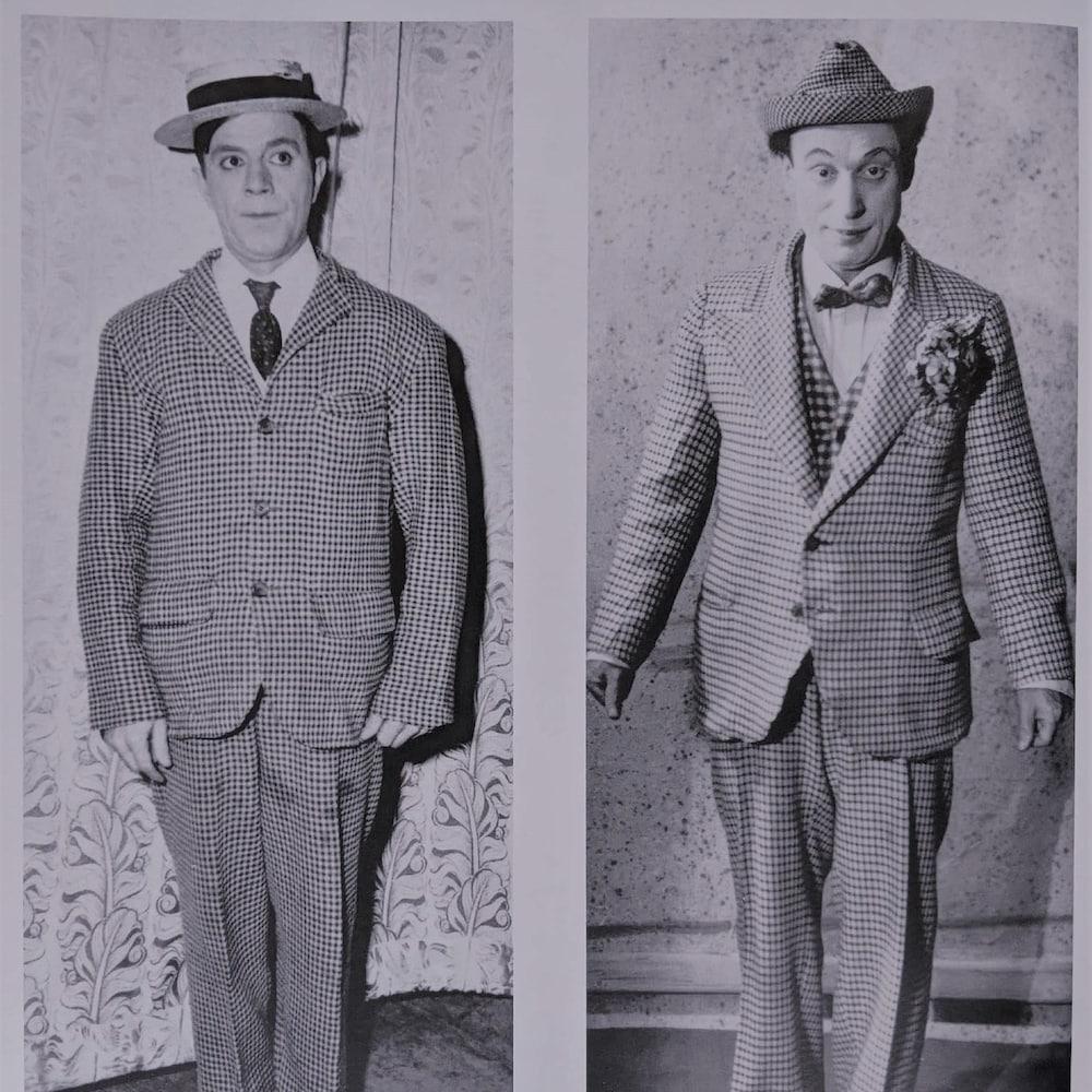 Les deux hommes sont habillés de manière similaire : un complet carotté, des souliers en cuir et un petit chapeau.