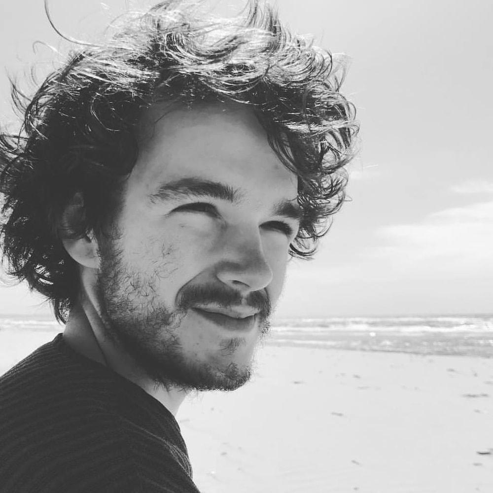 Olivier Renaud devant la mer en noir et blanc.