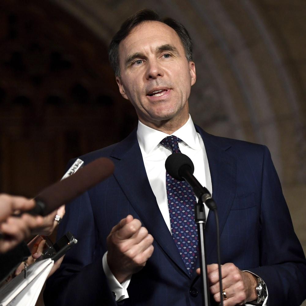 Il parle à des journalistes dans un couloir du parlement.