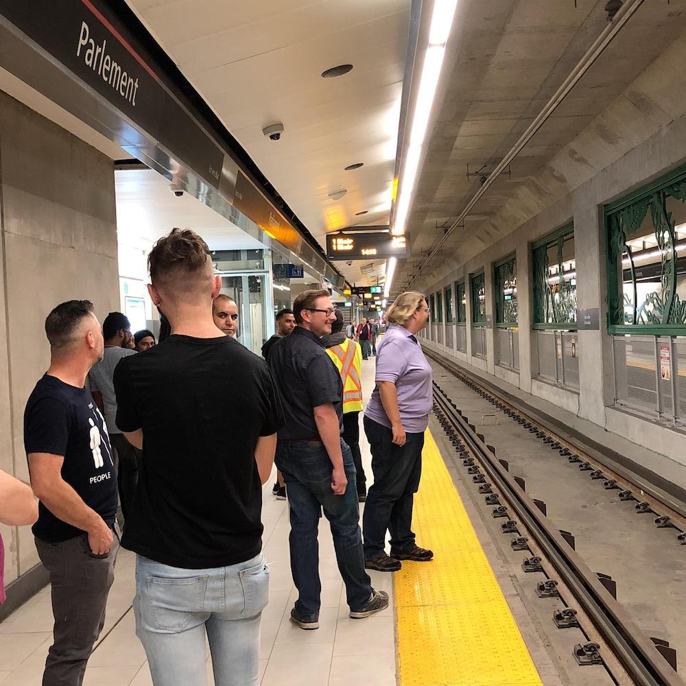 Des gens qui attendent sur le quai du train léger.