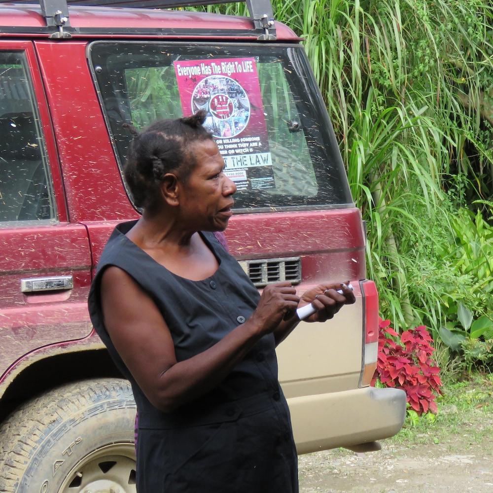 Anton Lutz discute avec une femme devant un véhicule.