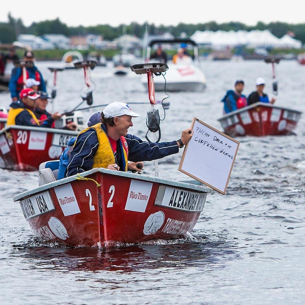 Paul Asmuth, dans un bateau, écrit des indications à un nageur sur un tableau blanc.