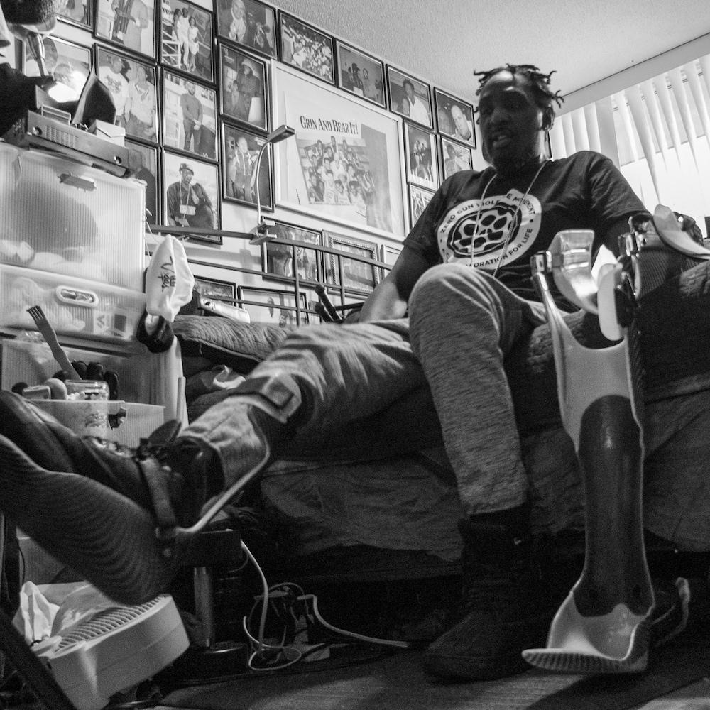 Un homme est assis sur un lit et essaye de lever sa jambe.