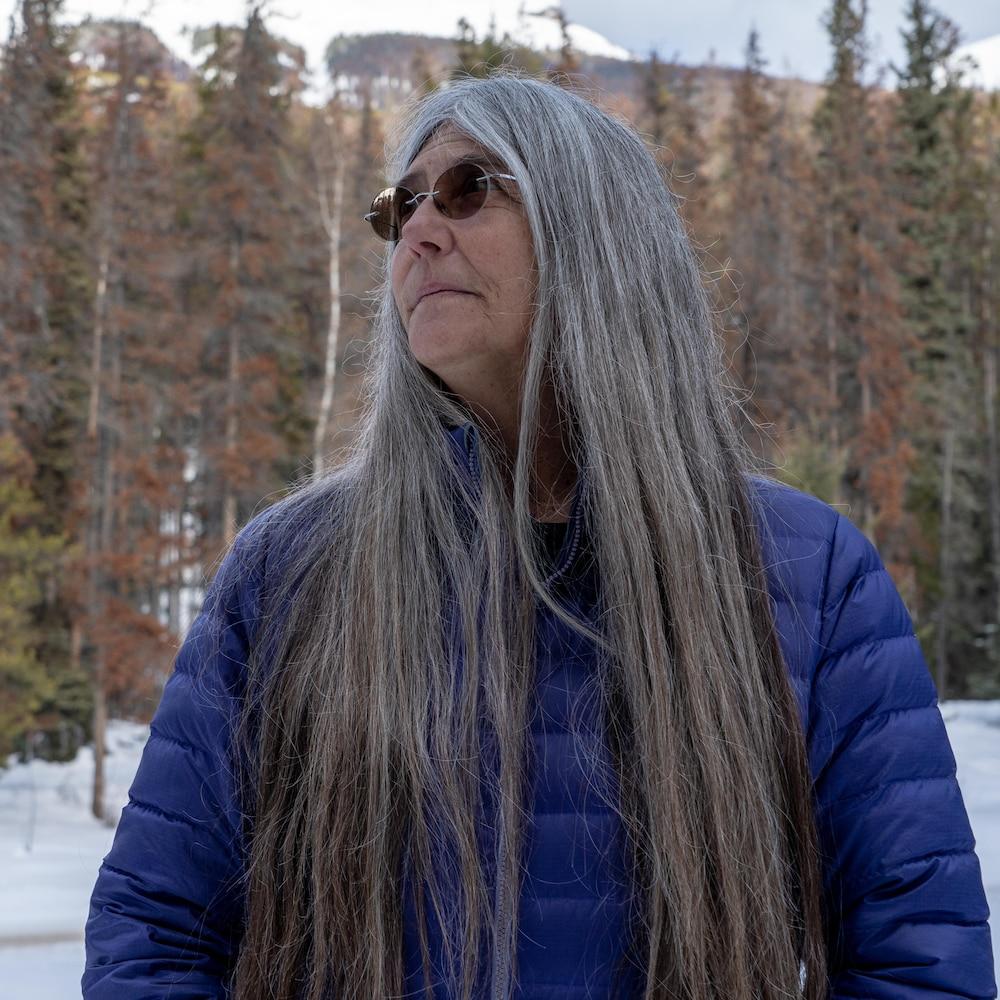 Une femme dans la soixantaine aux cheveux longs gris et avec des lunettes fumées pose de profil devant une forêt de conifères.