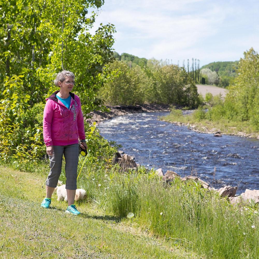 Pearl Pearson marche en bordure d'une rivière avec son chien.