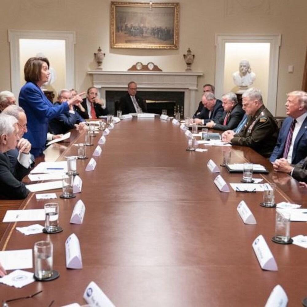 Nancy Pelosi, debout, devant plusieurs hommes, dont le président Trump.