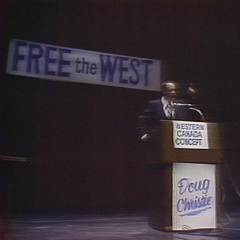 """Doug Christie en scène, avec une bannière indiquant """"Free the West"""" derrière lui."""