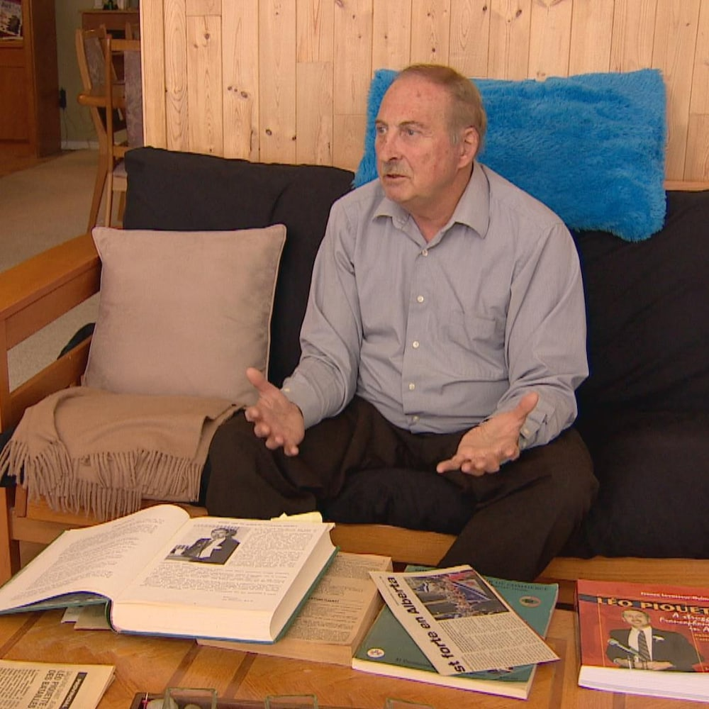 Léo Piquette dans son salon, avec des livres et des extraits de journaux sur une table.