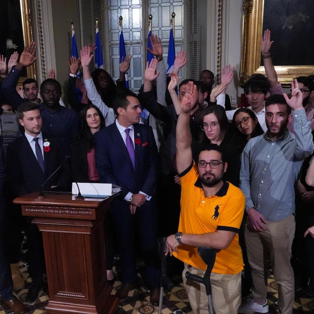 Trois députés des partis d''opposition entourés d'étudiants étrangers dans le foyer du parlement.