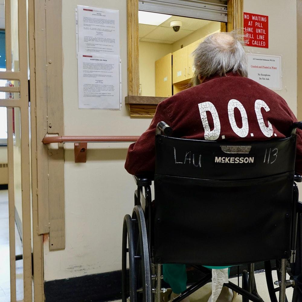 Un prisonnier se présente au comptoir où il doit recevoir des médicaments.