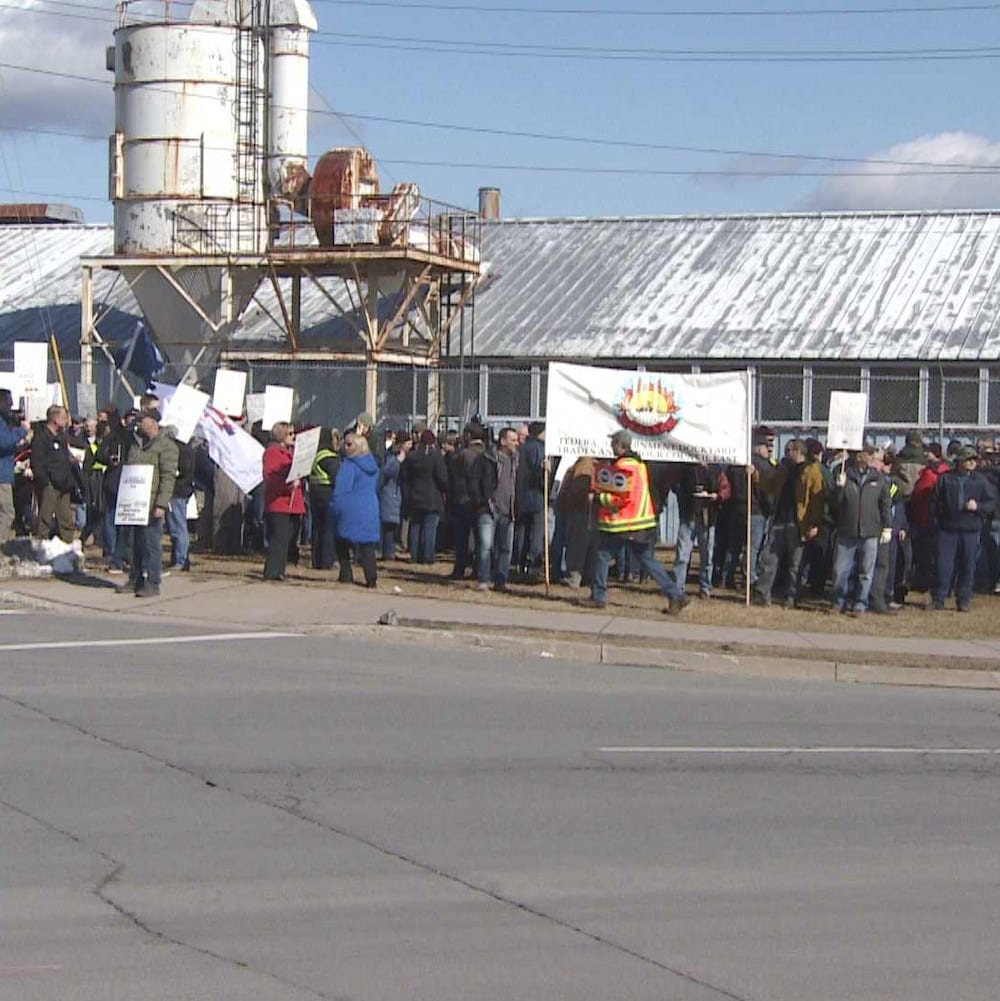 Des personnes manifestent contre les ratés du système de paye Phénix devant le chantier naval d'Halifax le 28 février 2018.