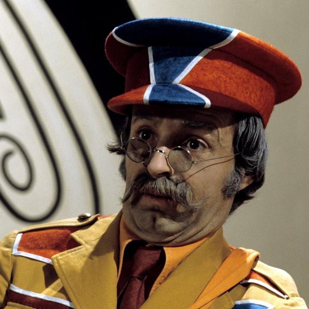 Dans la salle de jeux, Monsieur Simon (Luc Durand) se tient debout.