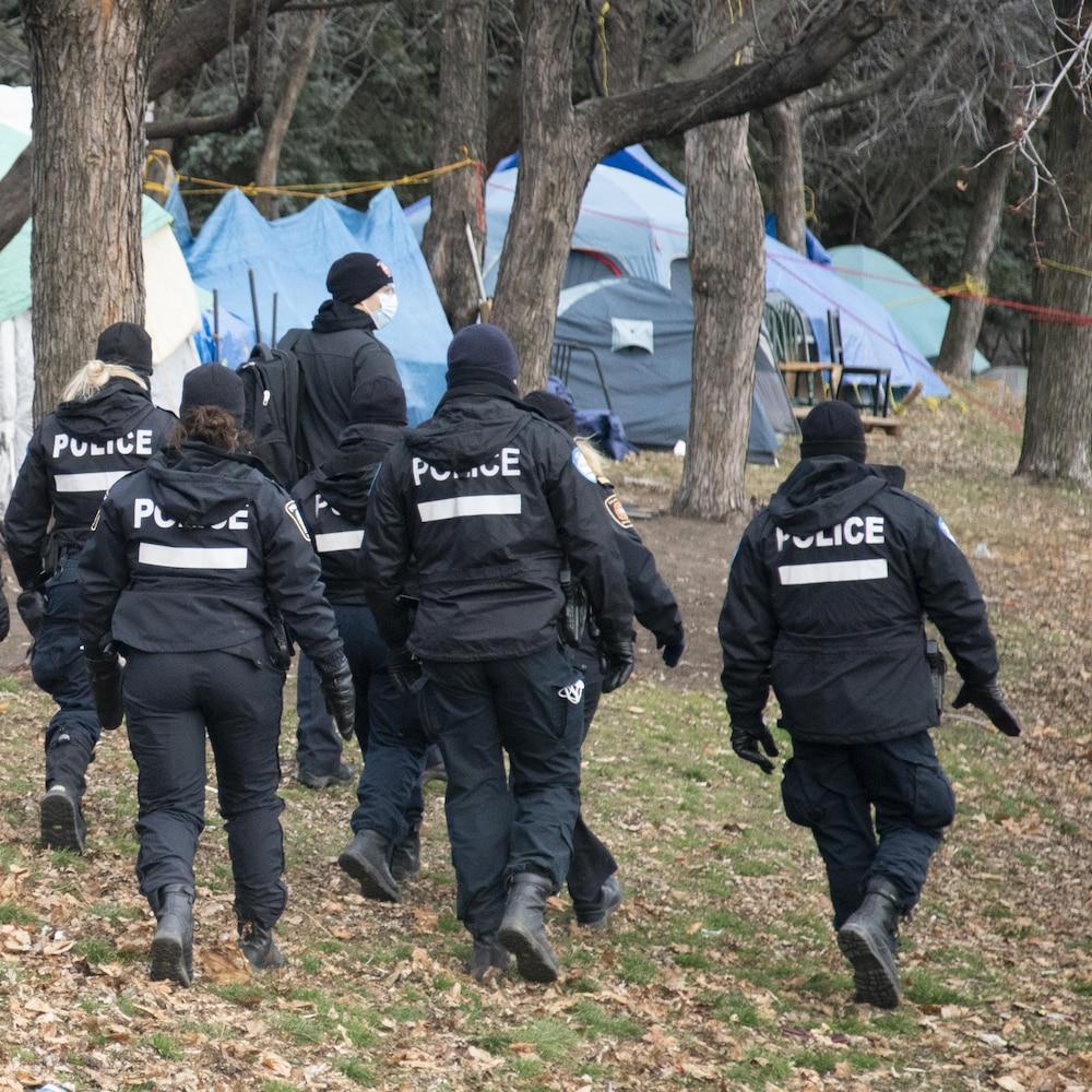 Des policiers marchent dans un parc.