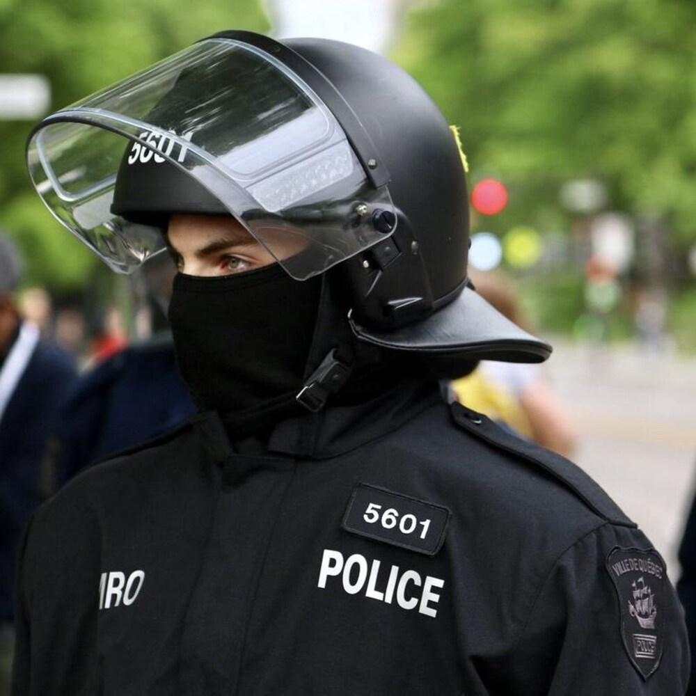 Photographie d'un policier de l'escouade antiémeute. Il est vêtu de noir et porte un casque de protection muni d'une visière. Son visage est en partie dissimulé par une cagoule.