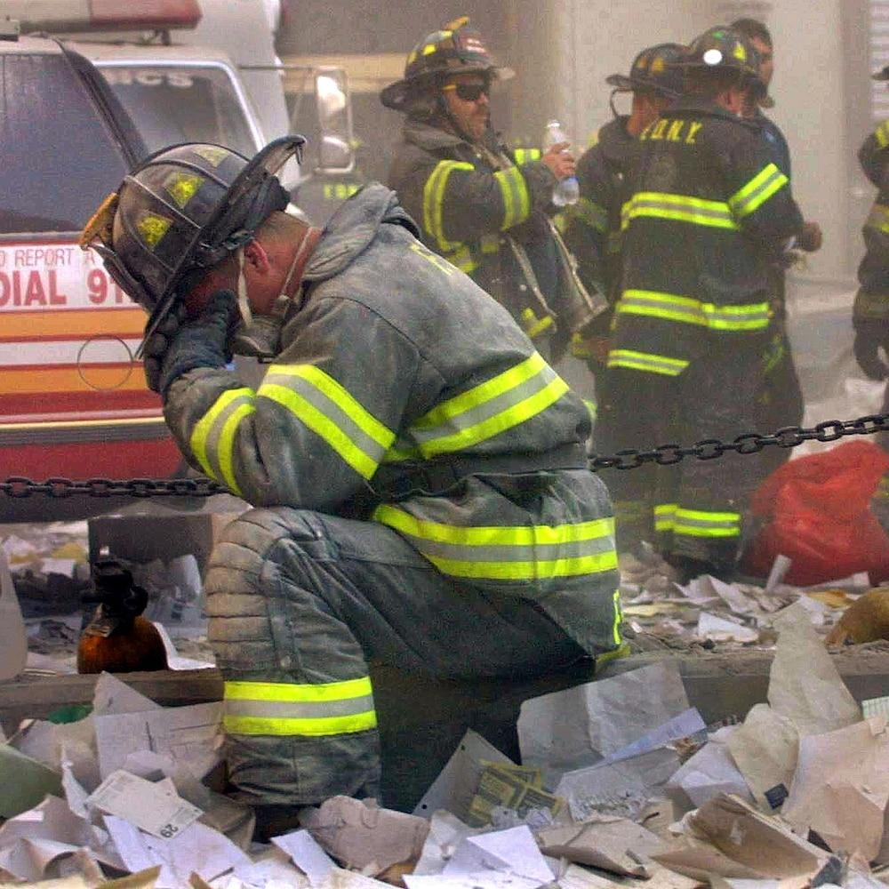 On voit le pompier, de profil, agenouillé et la main au visage. Des débris jonchent le sol autour de lui. En arrière plan, on voit ses collègues et des véhicules d'urgence.