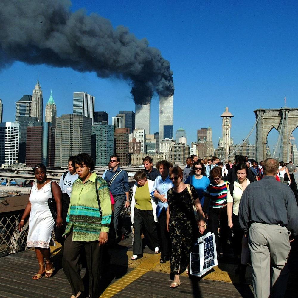 Des piétons vus de face marchent sur le pont de Brooklyn. En arrière-plan, on voit la structure emblématique du pont, les édifices de New York et les deux tours du World Trade Center d'où se dégage une épaisse fumée noire. Le ciel est bleu.