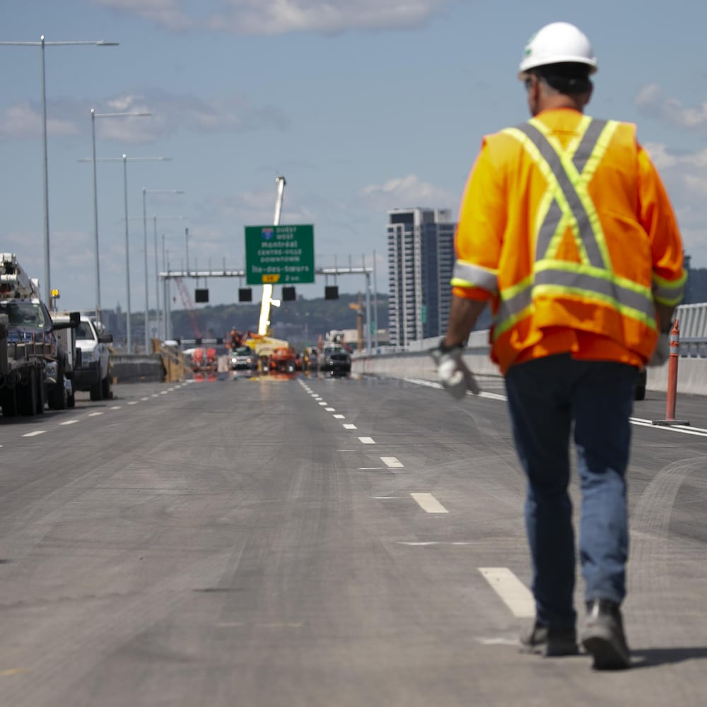 Un ouvrier marche sur la chaussée en direction nord.