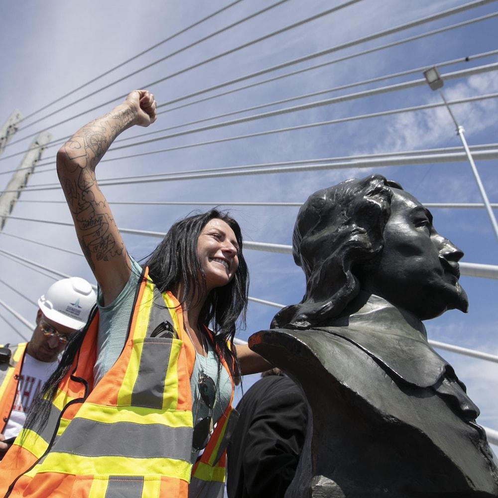 Une travailleuse, positionnée derrière le buste, lève le poing vers le ciel.