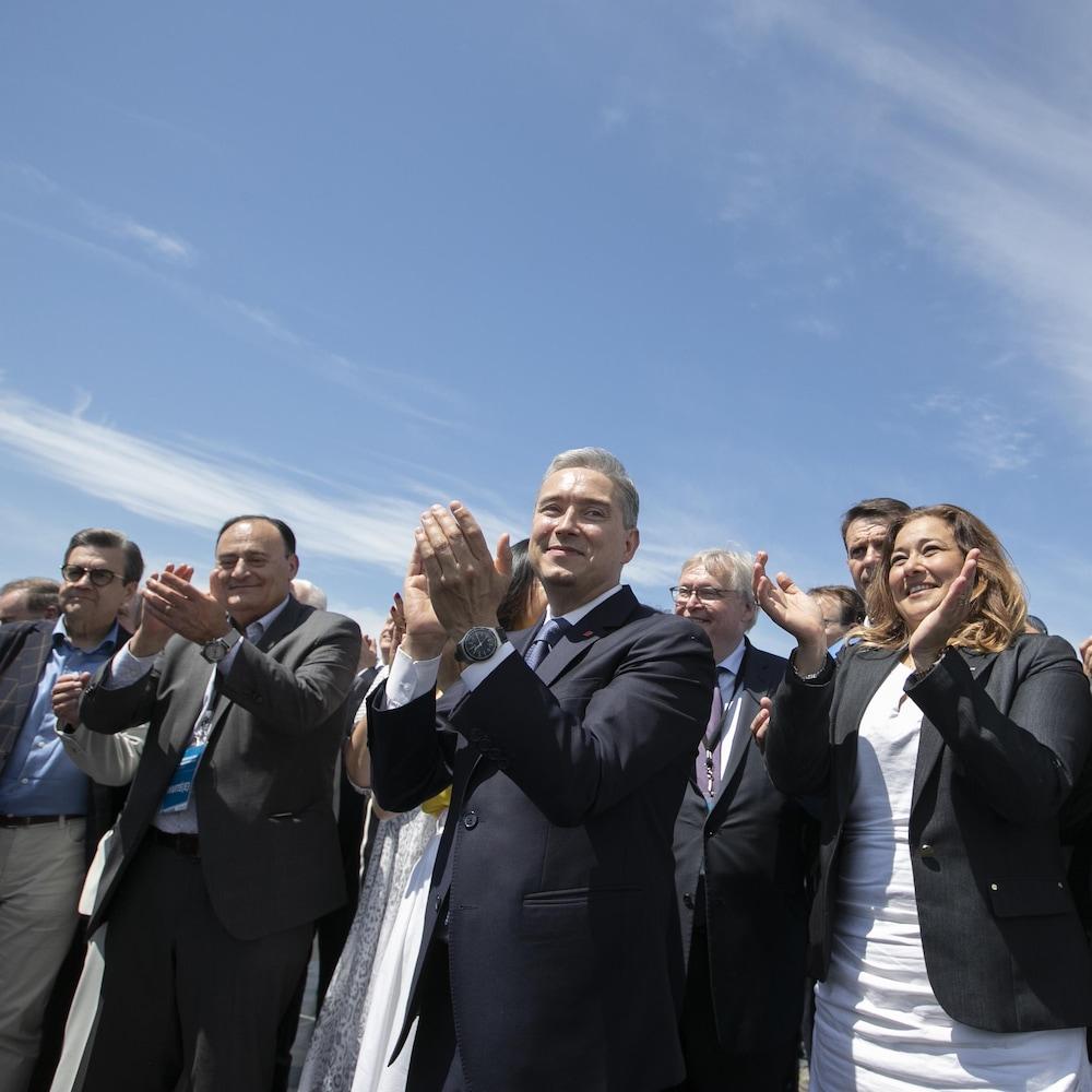 Plusieurs politiciens, dont François-Philippe Champagne, Denis Coderre et Gaétan Barrette, applaudissent.