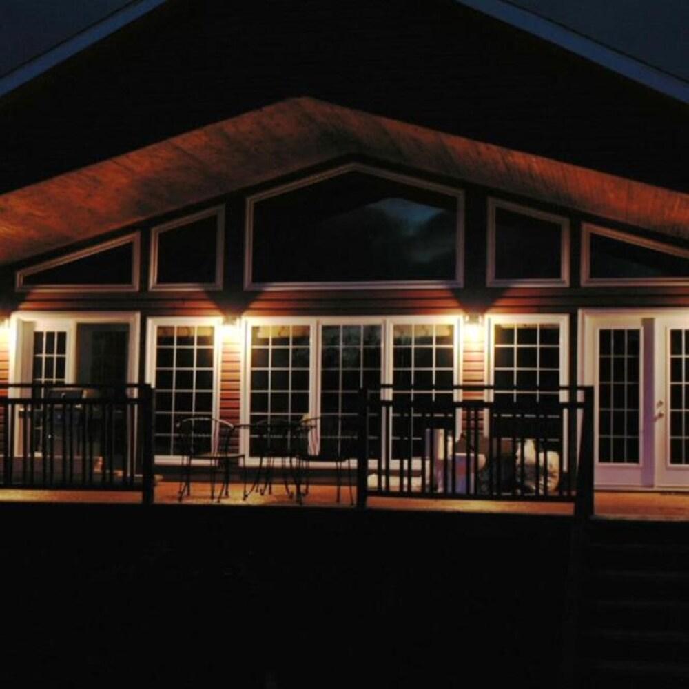 Une maison éclairée, à la tombée de la nuit.