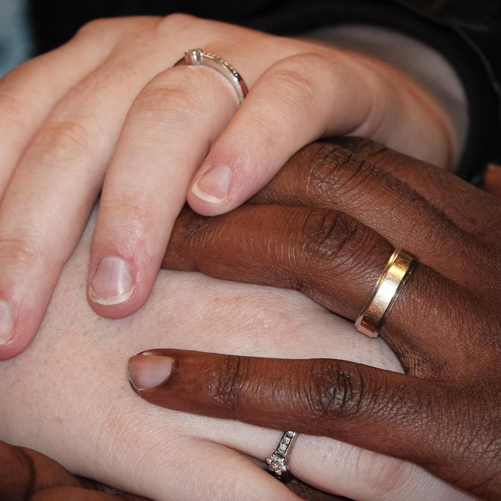 Les mains d'un homme et d'une femme portant chacun une alliance.