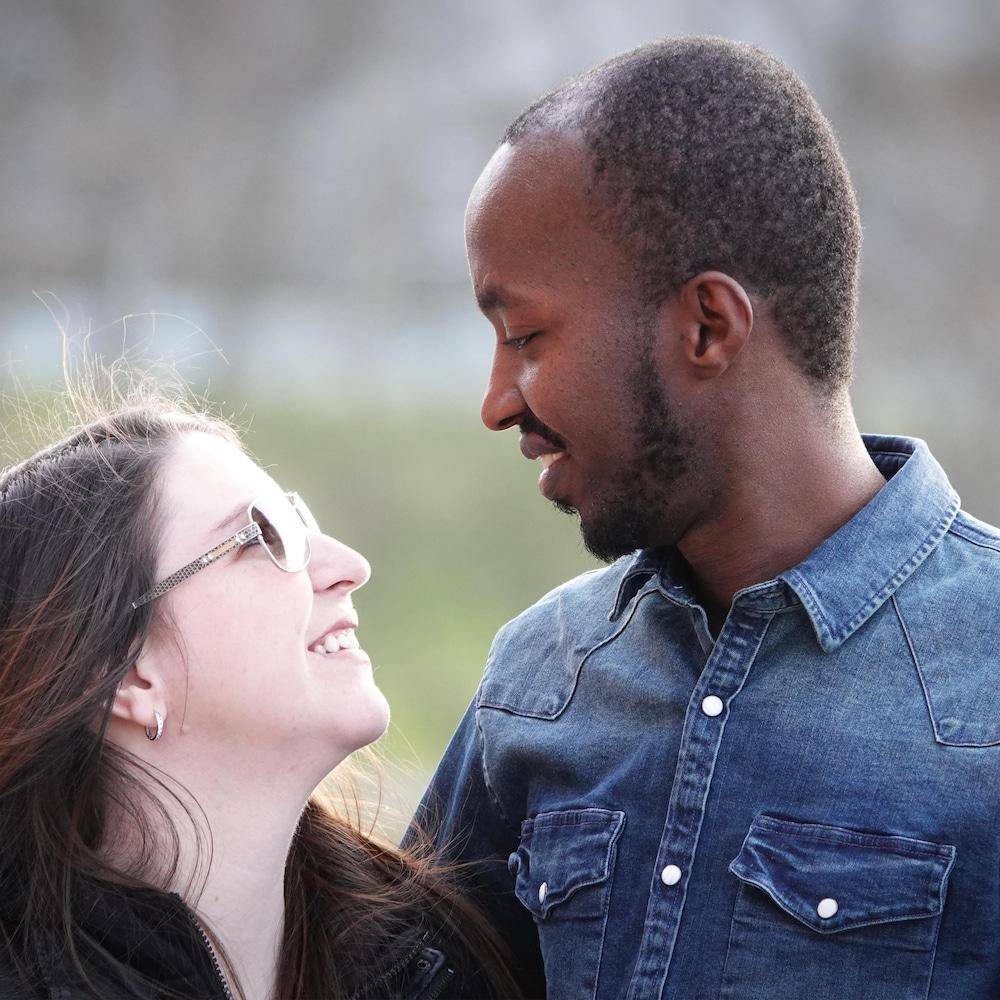 Un homme et une femme se regardent en souriant.