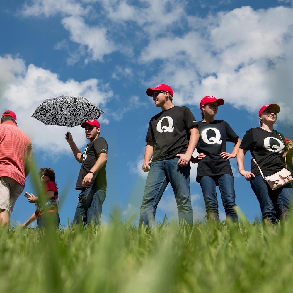 """Un groupe de personne portent des casquettes """"Make America Great Again"""" et des t-shirts noirs avec une grosse lettre Q, représentant la mouvance conspirationniste QAnon."""