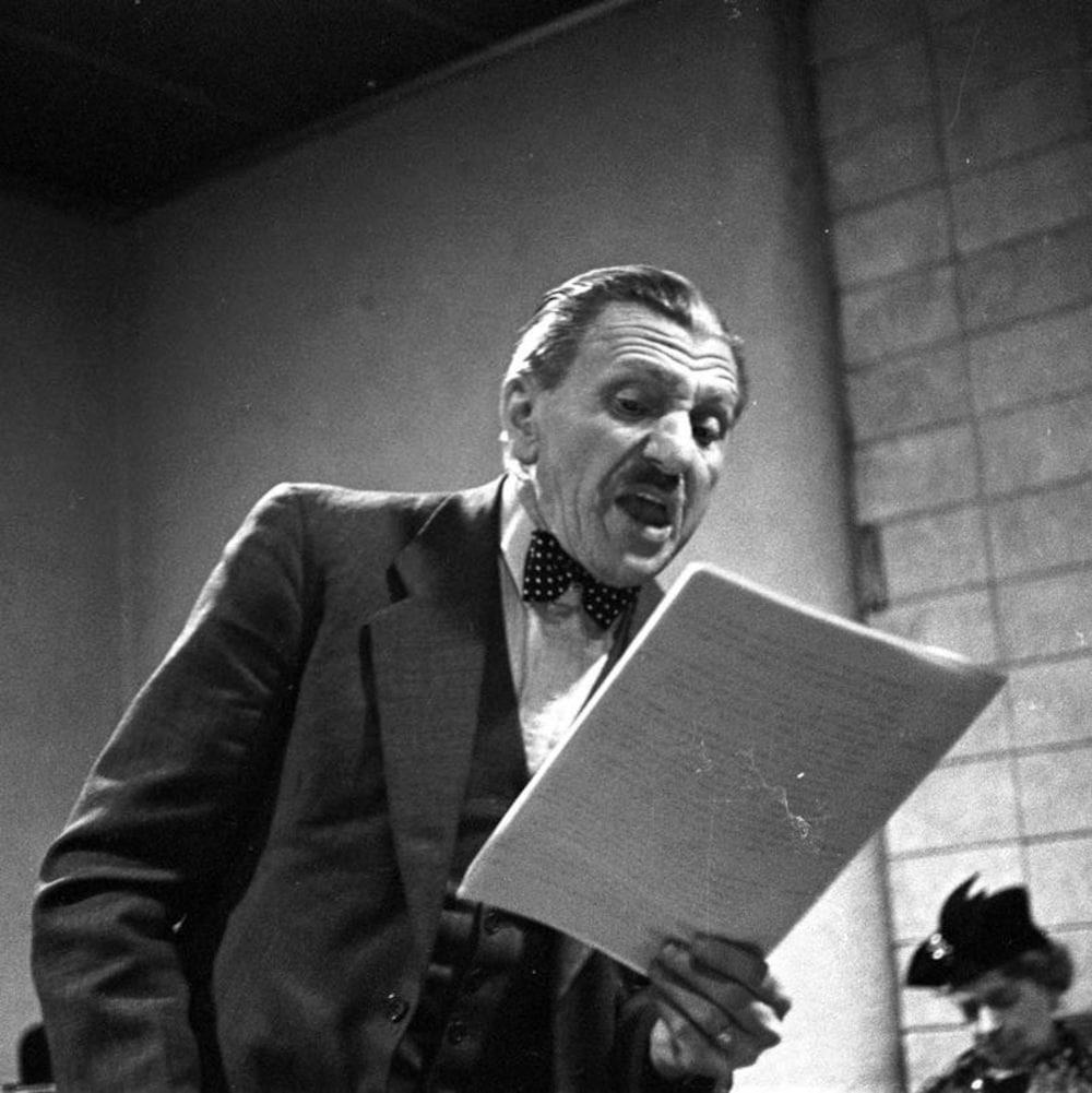 Dans un studio de radio, Hector Charland interprétant le rôle de Séraphin, avec son texte à la main, derrière un micro sur pied.