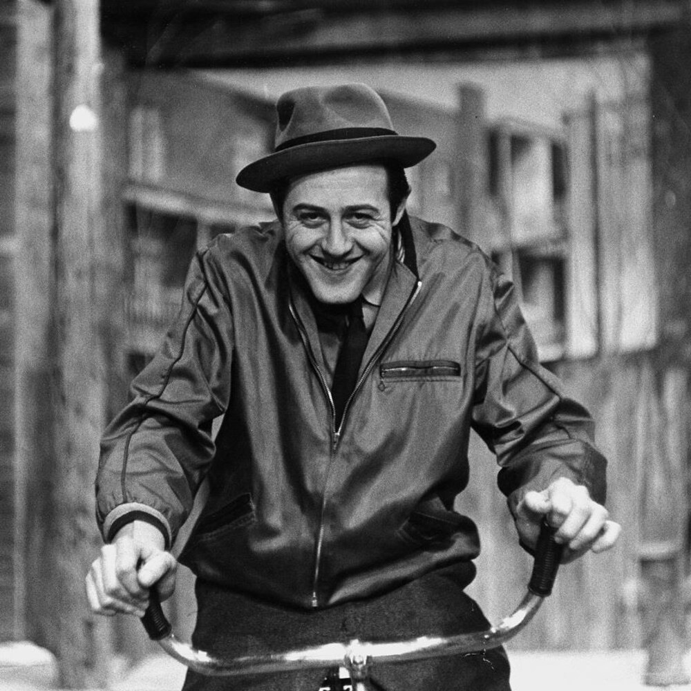 Dans une ruelle, Médée (Raymond Lévesque) assis sur sa bicyclette.