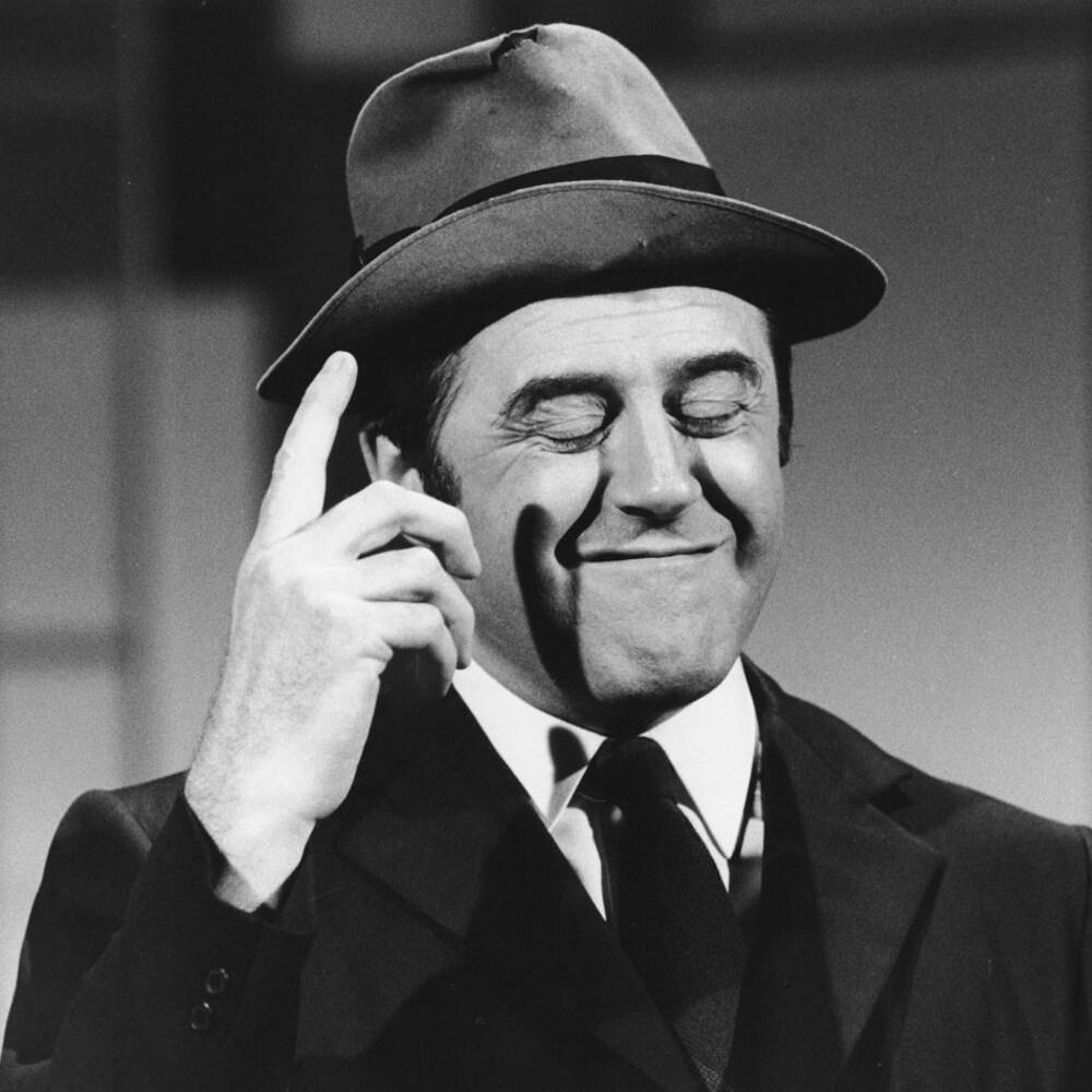 Raymond Lévesque avec un chapeau sur la tête, interprétant un monologue sur scène.