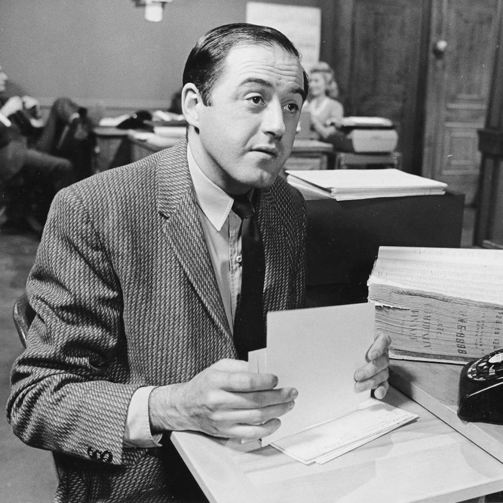 Raymond Lévesque, en veston, dans un décor de bureau.
