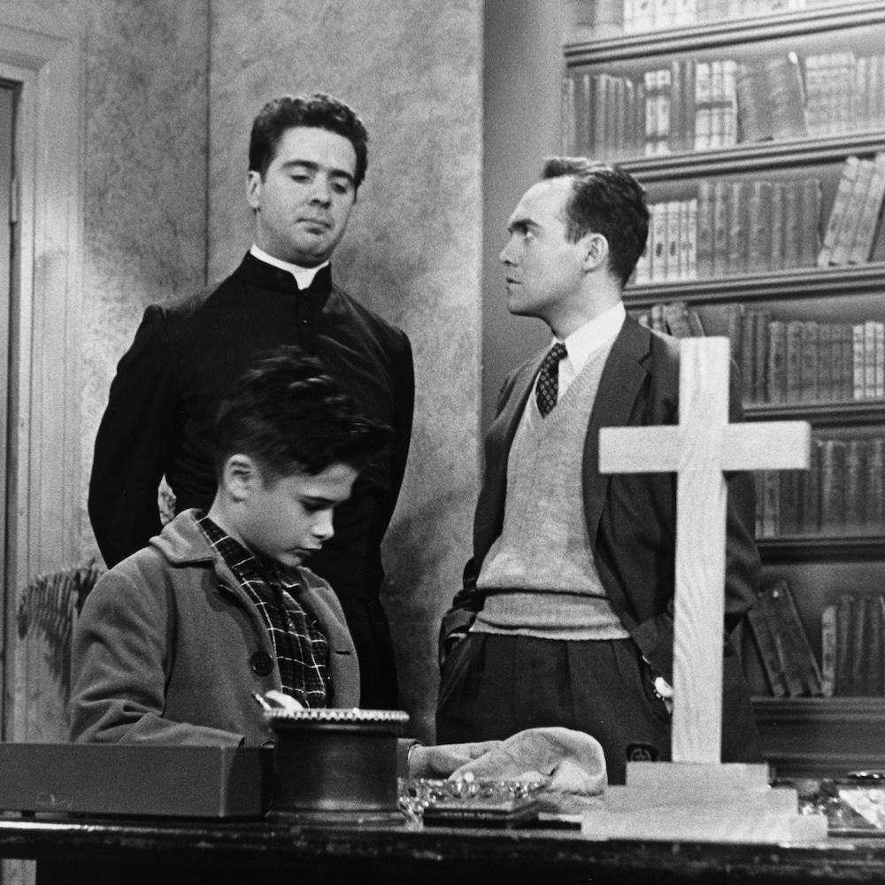 Un jeune comédien est assis à un pupitre tandis que le personnage du curé discute avec un autre personnage. Un croix est à l'avant plan.