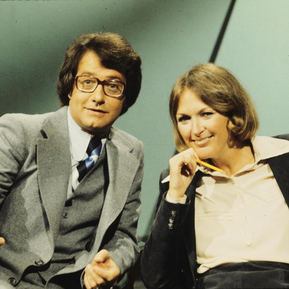 Gilles-Claude Thériault gesticule et Madeleine Poulin sourit, un crayon à la main.