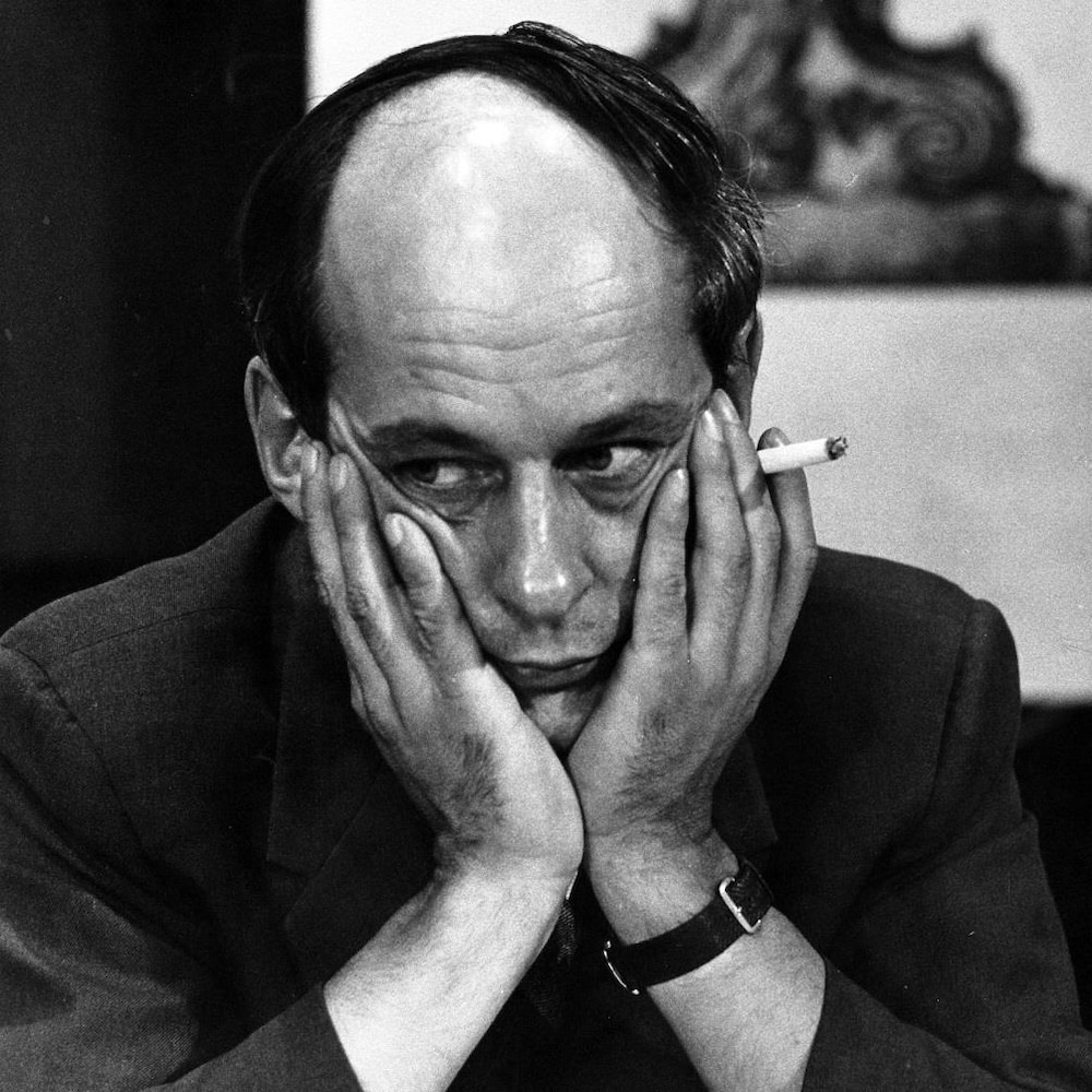 L'animateur René Lévesque, l'air pensif, son visage appuyé et encerclé de ses mains, une cigarette entre les doigts.