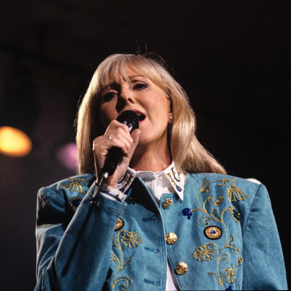 Renée Martel qui chante micro à la main.