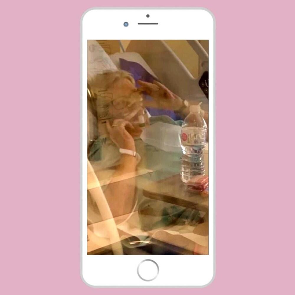 Rita Doiron dans un lit d'hôpital téléphone en main.