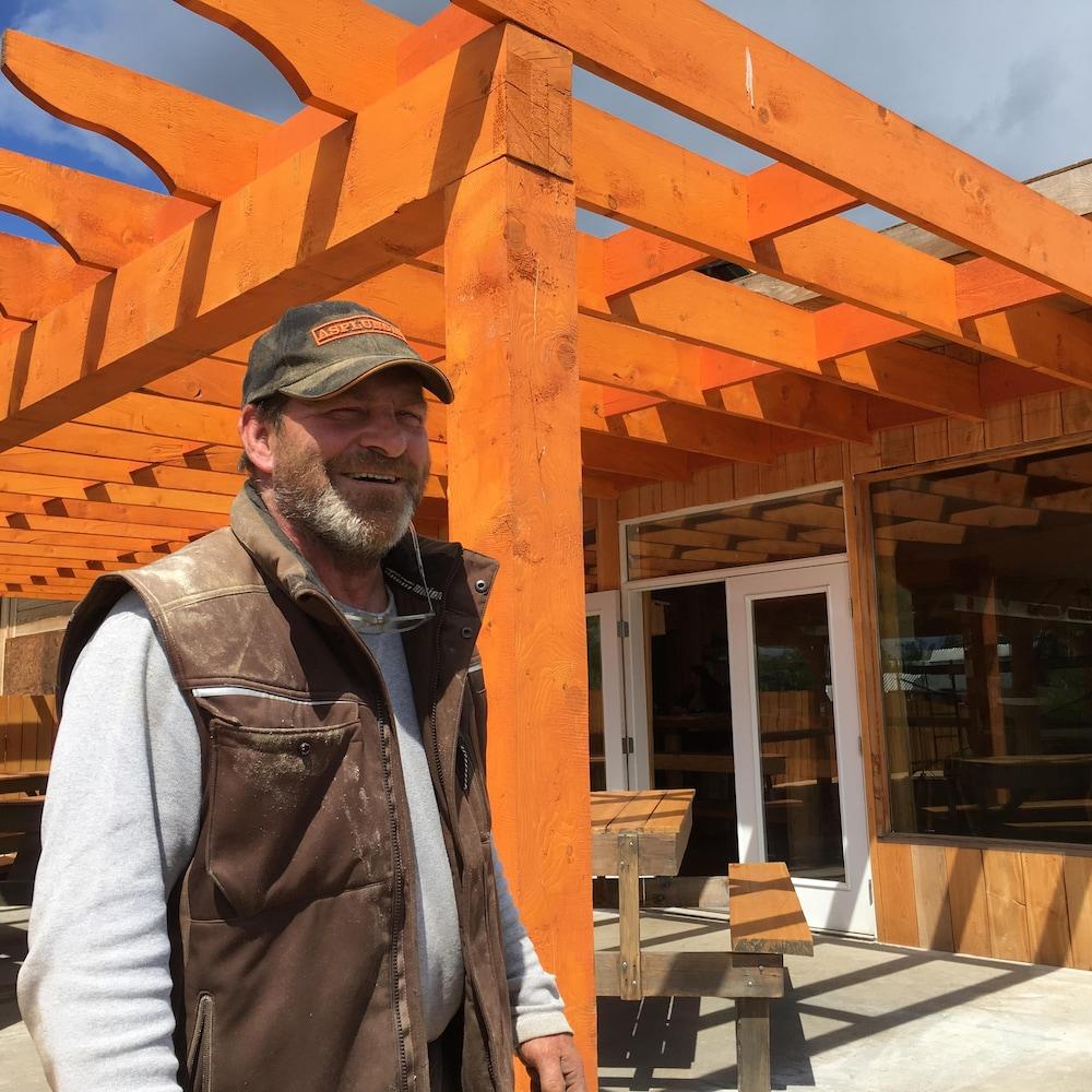 Un homme devant un commerce construit en bois, avec des tables de pique-nique dehors devant la porte.