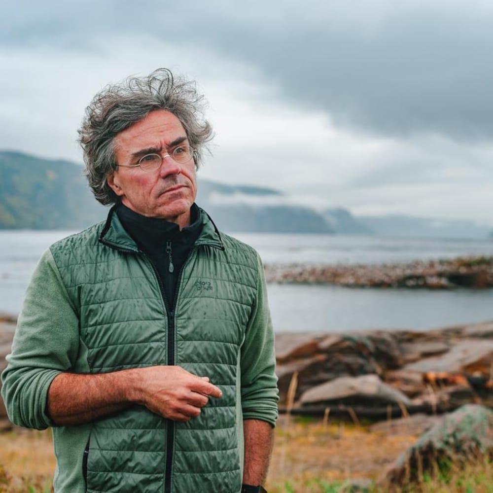 Robert Michaud regarde au loin sur le rivage à Tadoussac.