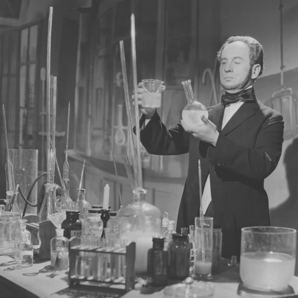 Un homme tient un bécher et un flacon de laboratoire dans ses mains.