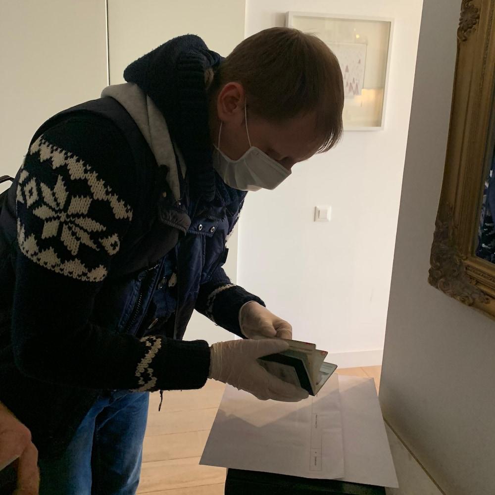 Un homme portant un masque feuillette un passeport et d'autres documents.
