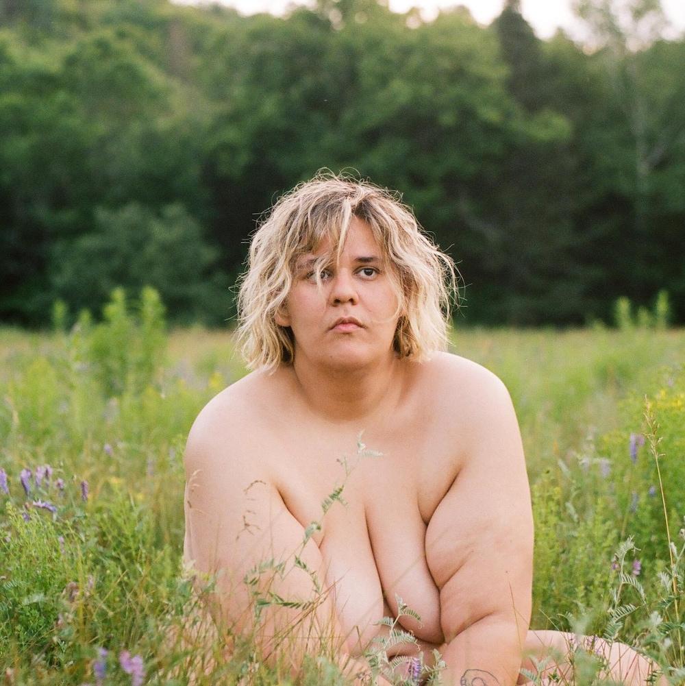 L'artiste est assise nue dans l'herbe.
