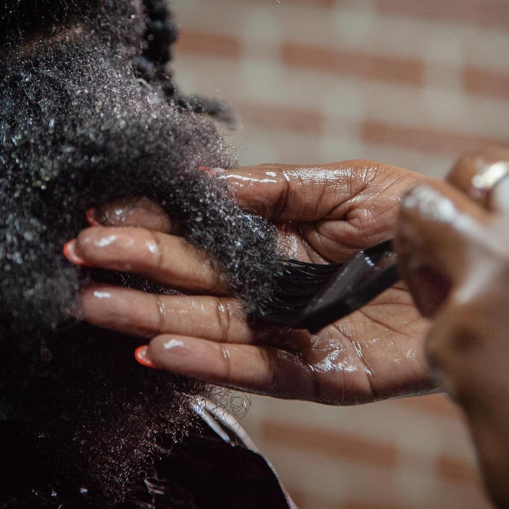 Plaquie tient une mèche de cheveux dans sa main en appliquant l'huile à l'aide d'un pinceau.