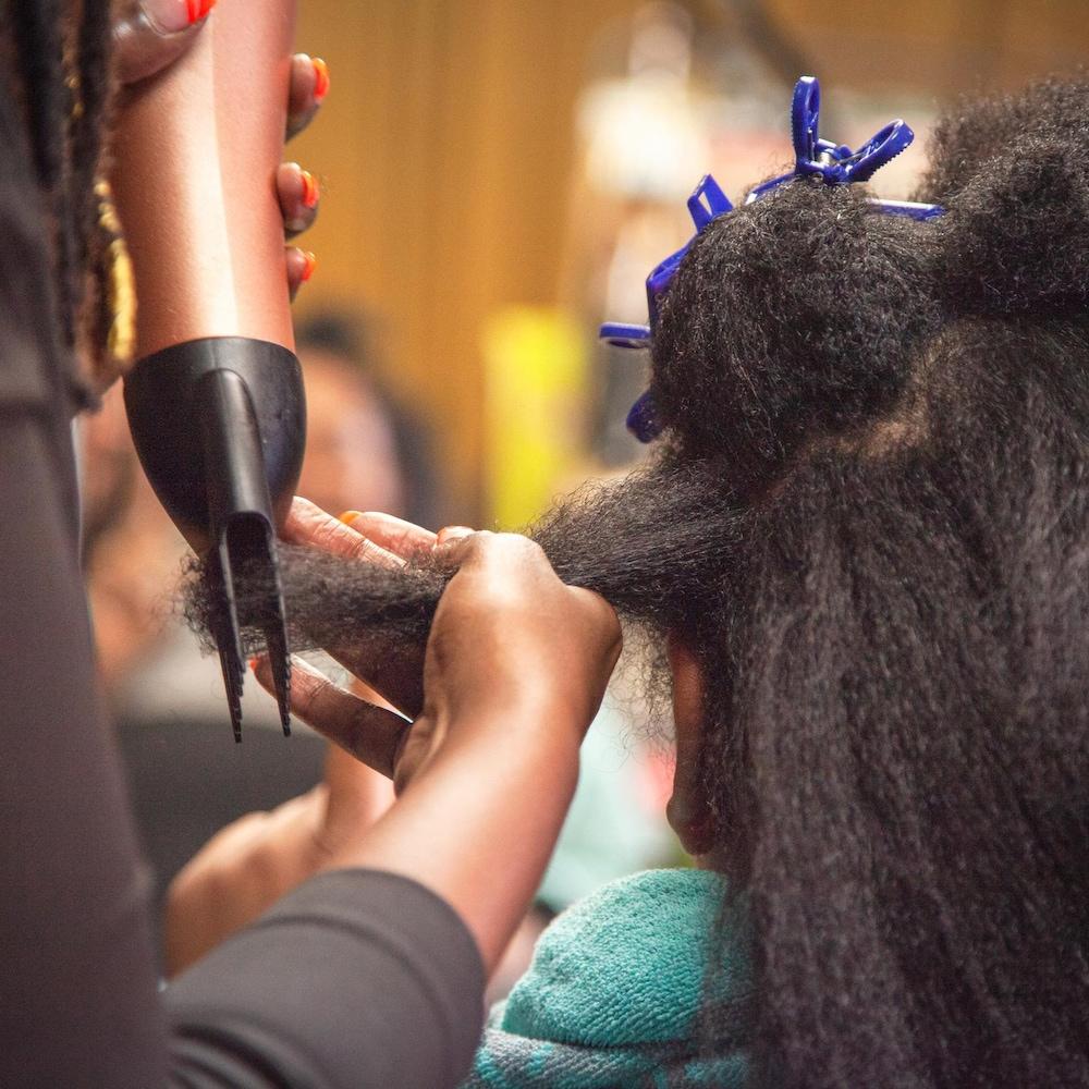 Plaquie utilise un séchoir avec un peigne pour démêler les cheveux de Vanina.