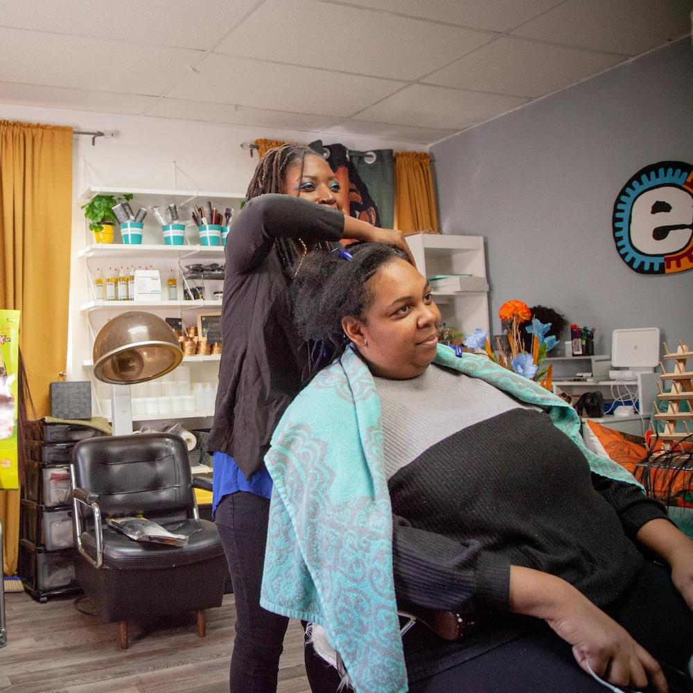 Vanina est sur la chaise de coiffure tandis que Plaquie la coiffe.