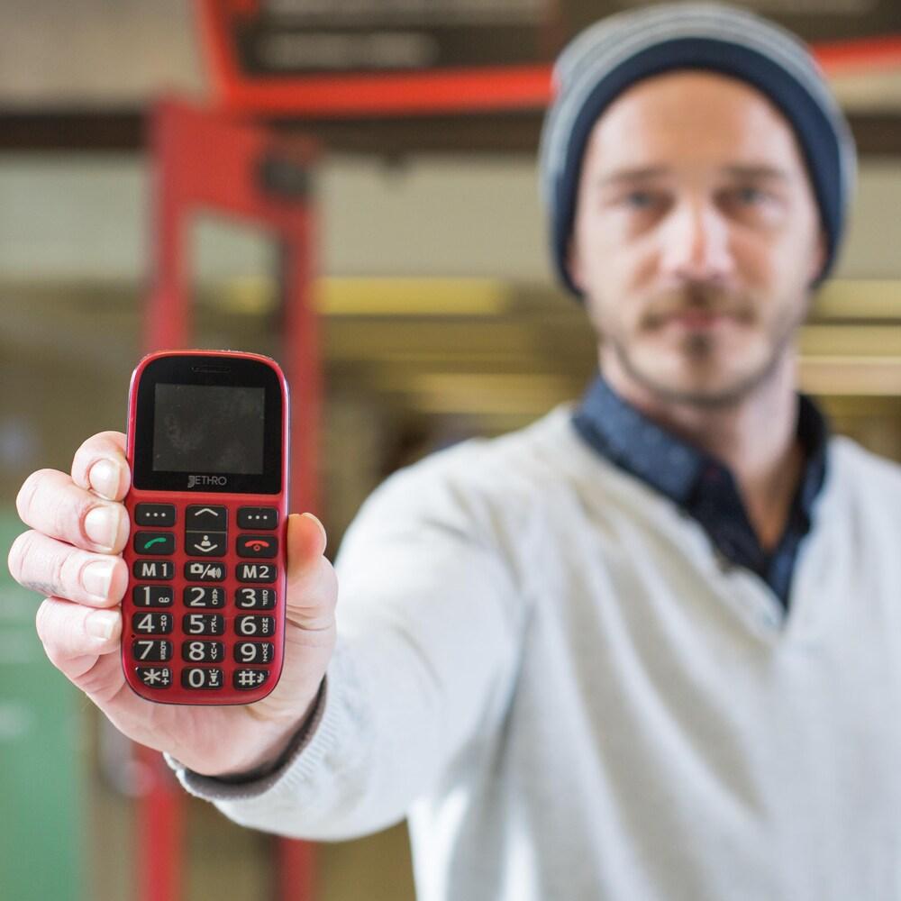Samuel Veissière montre son téléphone cellulaire à pavé numérique à la caméra.