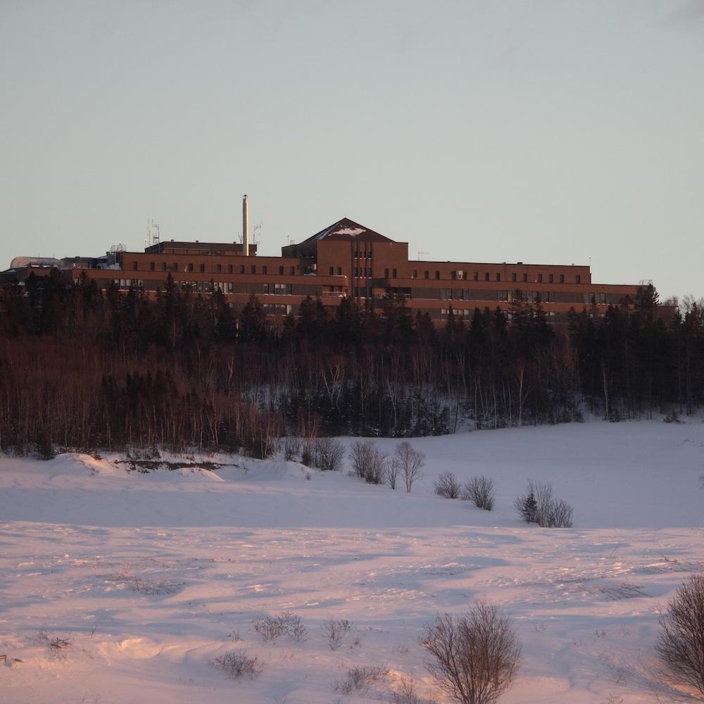 Le sanatorium de Mont-Joli, au sommet d'une petite montagne surplombant un champ.
