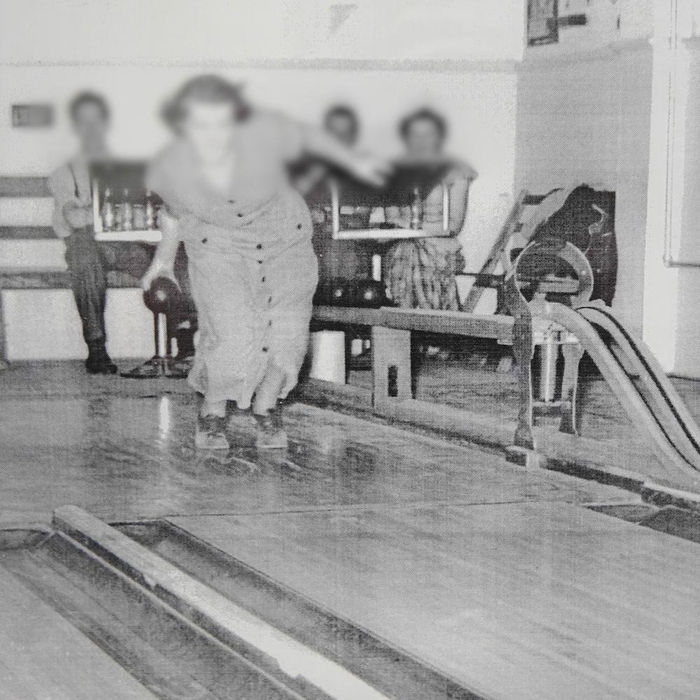 Une photographie en noir et blanc d'une dame s'élançant sur une allée de quilles au sanatorium de Mont-Joli.