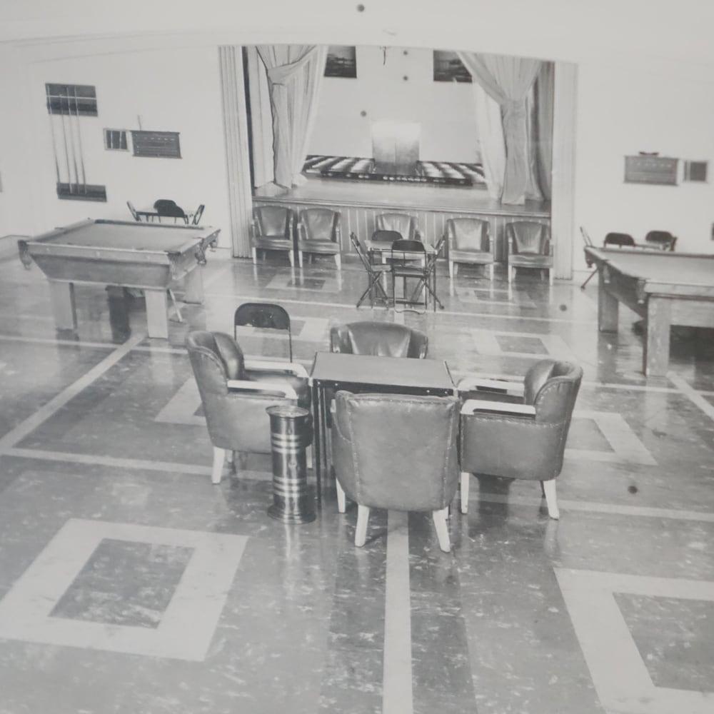 Photographie en noir et blanc d'une salle avec deux tables de billard et des fauteuils en cuir avec des cendriers.