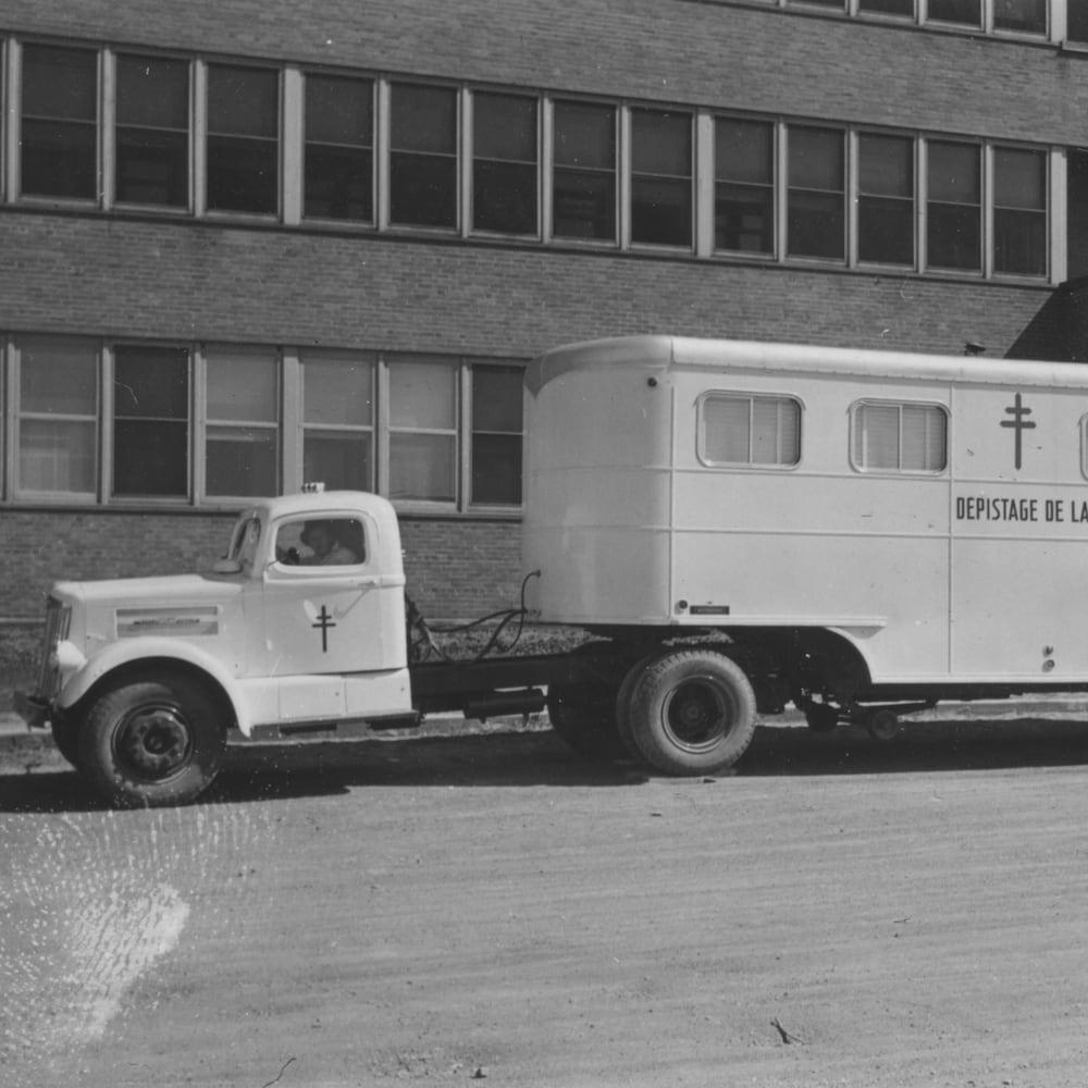 Photographie en noir et blanc de la roulotte de dépistage de la tuberculose devant le sanatorium de Mont-Joli.