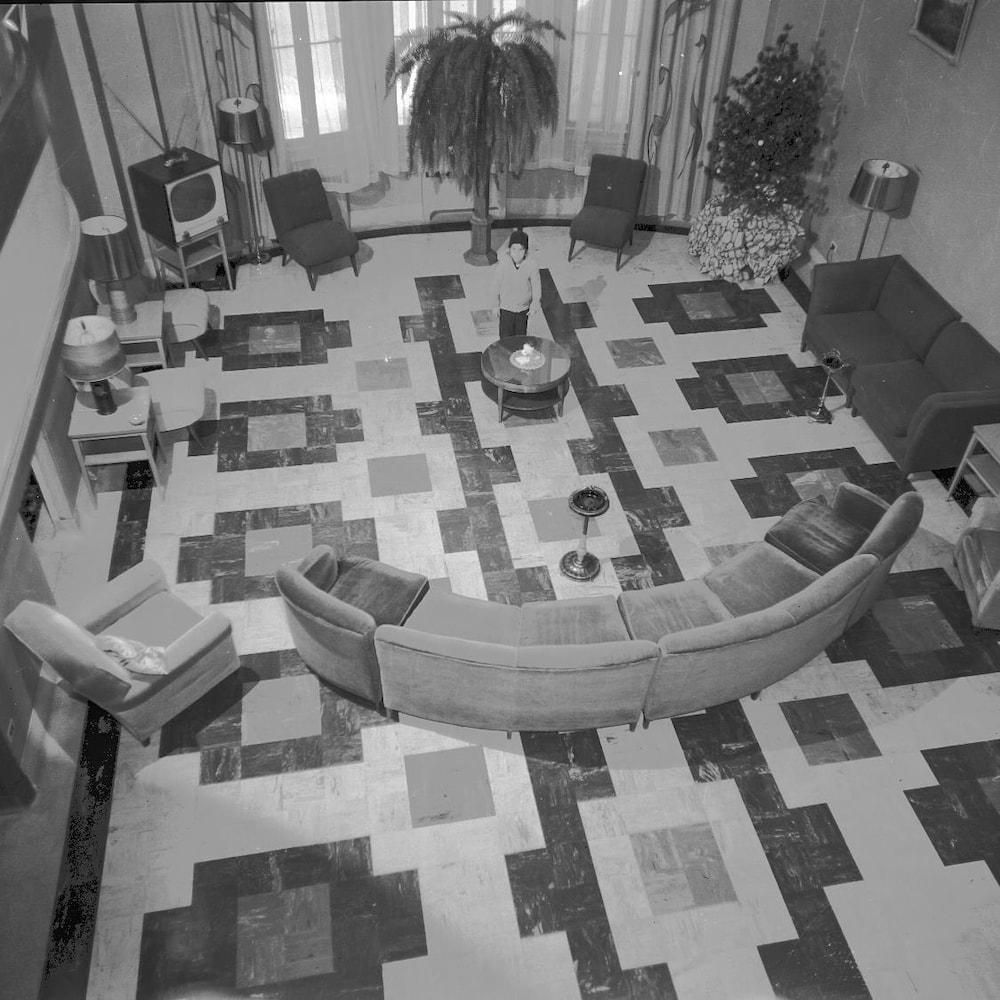 Une photographie en noir et blanc d'un enfant au centre d'une pièce de repos avec des fauteuils et des sofas.